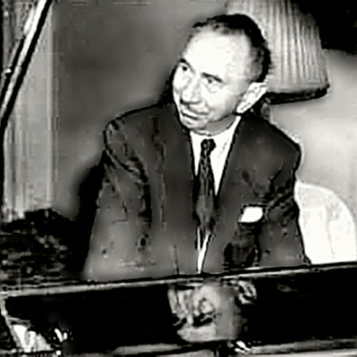 Composer Rudolf Friml leaning against his piano.